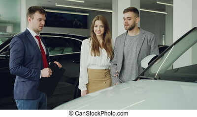 Friendly car salesman is talking to confident young man telling him about new vehicle model while pretty woman is standing near her husband holding his arm and smiling.