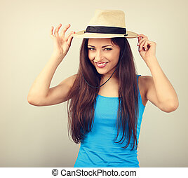 Friendly casual calm woman in blue top holding straw hat and looking happy with long volume hairstyle on toned vintage copy space