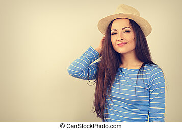 Friendly casual calm woman thinking in blue top and straw hat looking happy on toned vintage color copy space