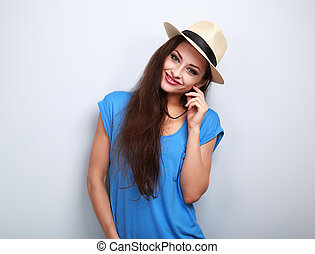 Friendly casual woman in hat looking happy on blue background