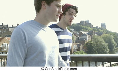 Friendly chat - Two young men walking along a bridge talking...