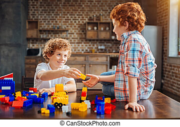 Friendly children playing with construction set