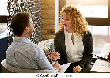 Friendly couple having conversation in the cafe