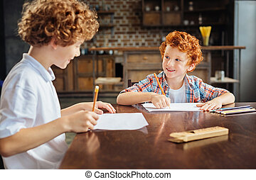 Friendly curly haired children drawing together