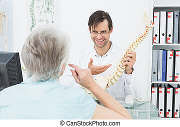 Friendly doctor explaining spine to