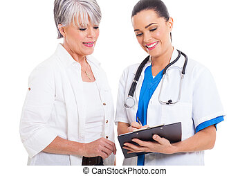 doctor helping senior woman with medical form