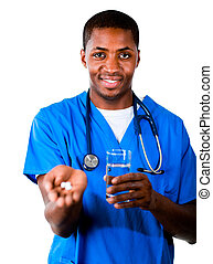 Friendly doctor in scrubs with pills and glass of water