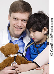 Friendly doctor playing with five year old disabled patient during office visit by playing with teddy bear doll together