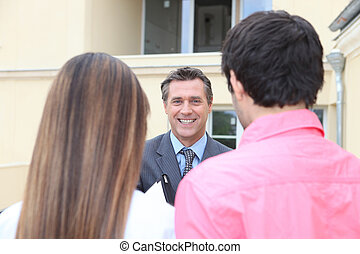 Friendly estate-agent welcoming couple