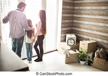 Friendly family is standing near window and looking outside. There are man boxes on the right side of apartment. People are talking about something.