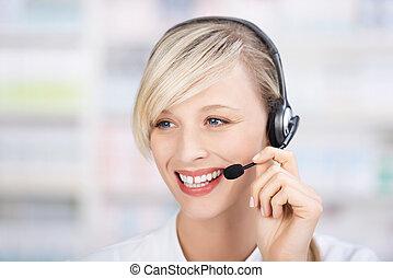 Friendly female pharmacist using headsets