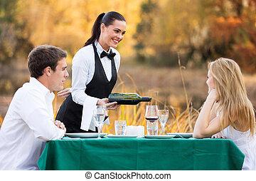 waitress pouring wine for romantic couple
