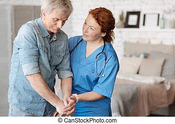 Friendly focused nurse encouraging her elderly patient