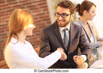 friendly handshake between colleagues in the office