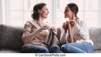 Friendly happy mature mum and adult daughter chatting knitting together