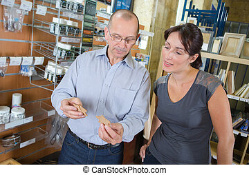 friendly hardware store assistant helping woman choosing taps