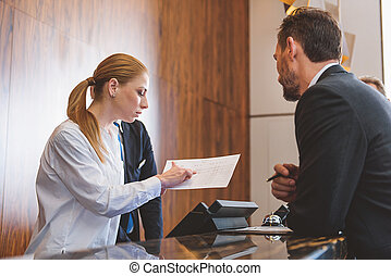 Friendly hotel worker at reception desk