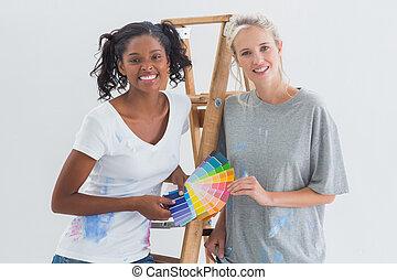 Friendly housemates choosing colour for wall looking at camera