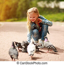 Friendly joyful girl child feeds pigeons in city summer park