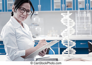 Friendly looking female professional taking notes in lab -...