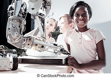 Friendly looking girl smiling after examining robot