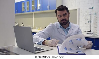 Friendly looking scientist smiling into camera while working
