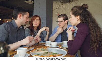 Friendly male and female colleagues are eating pizza in cafe...