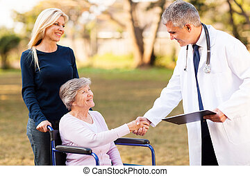male doctor handshaking with senior patient