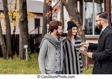Friendly male real estate agent handing house key to a smiling young couple in office
