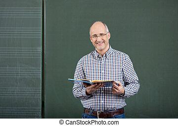 Friendly male teacher teaching form a set of class notes...