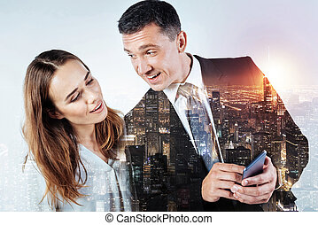 Friendly man showing a new smart phone to his pretty colleague