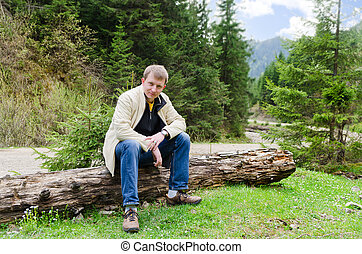 Friendly man sitting on a tree trunk