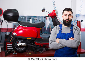 friendly man worker displaying his workplace in motorcycle workshop