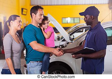 friendly mechanic handshaking with family - friendly auto...