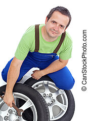 Friendly mechanic with car tires