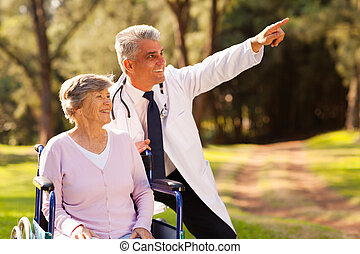 friendly medical doctor and senior patient outdoors for a walk