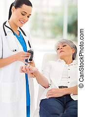 medical nurse checking middle aged patient's pulse