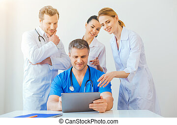 Friendly medical professional looking at laptop and smiling...