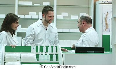 Friendly medical team in lab coat discussing new pills in pharmacy