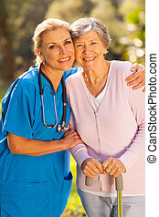 caregiver hugging senior patient outdoors