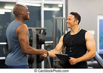 middle aged gym trainer greeting client