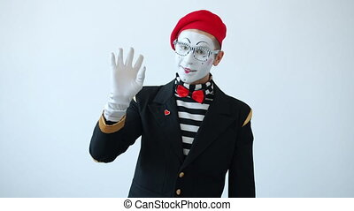 Friendly mime artist waving hand saying hello greeting people and looking at camera standing on white background. Gestures and body language concept.