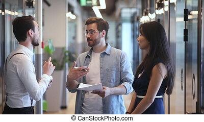 Friendly multiethnic business people talking standing in ...