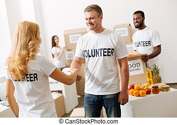 Friendly nice man shaking hands with new volunteer