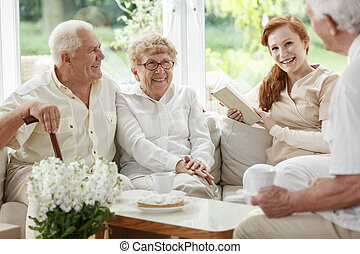 Friendly nurse enjoys meeting with elder people while sitting on beige coach