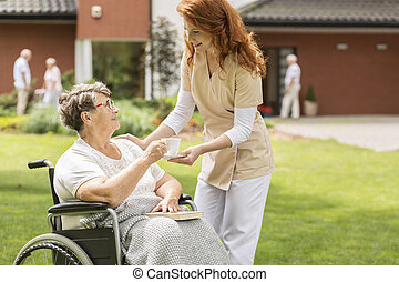 Friendly nurse giving tea to disabled senior woman in the wheelchair in the garden