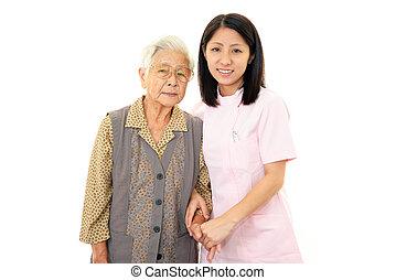 Friendly nurse wite elderly woman
