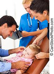 pediatrician examining little girl's ear