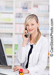 Friendly pharmacist portrait talking at the phone