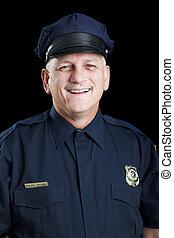 Portrait of friendly, smiling police officer on black background.